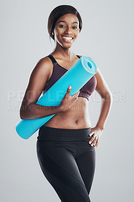 Buy stock photo Studio portrait of an attractive and fit young woman holding an exercise mat against a grey background