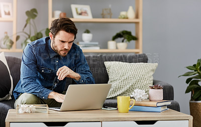 Buy stock photo Shot of a focused young man doing  blogging on his computer at home