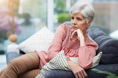 Buy stock photo Shot of a mature woman looking thoughtful while relaxing on her couch at home