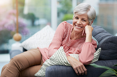 Buy stock photo Portrait of a cheerful mature woman posing with her hand on her chin while relaxing on a sofa at home