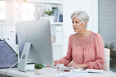 Buy stock photo Shot of a mature businesswoman working on a computer in her office