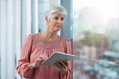 Buy stock photo Shot of a mature businesswoman using her digital tablet at work
