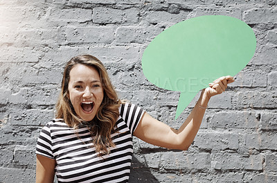 Buy stock photo Shot of a cheerful young woman holding a speech bubble against a brick wall outside