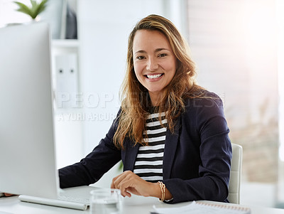 Buy stock photo Portrait of a cheerful businesswoman working on a computer in her office