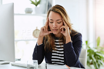 Buy stock photo Shot of an attractive businesswoman suffering from a headache in her office at work
