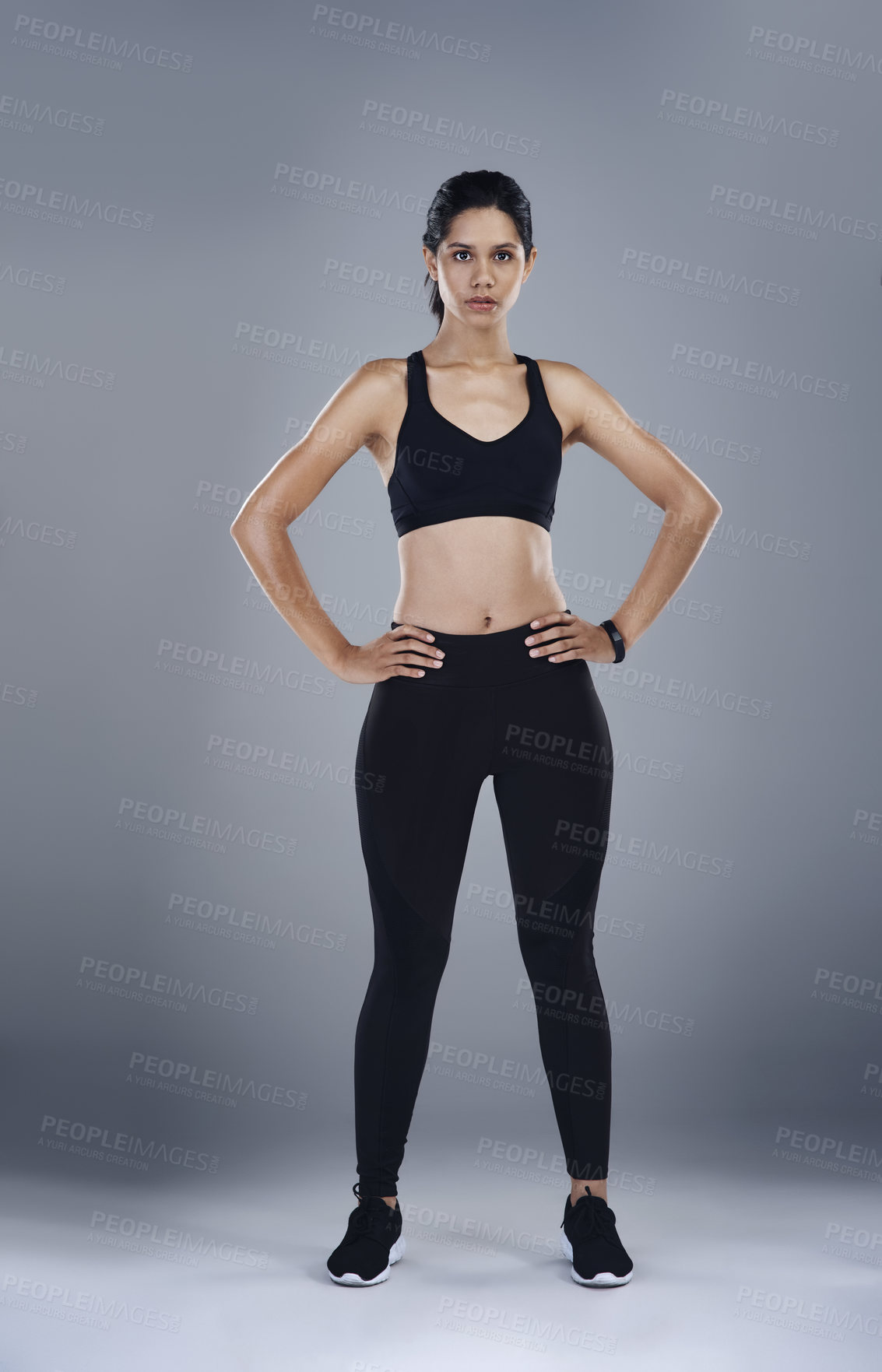 Buy stock photo Full length shot of a sporty young woman posing with her hands on her hips  against a grey background