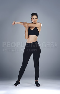 Buy stock photo Full length shot of a sporty young woman standing and stretching her arm against a grey background