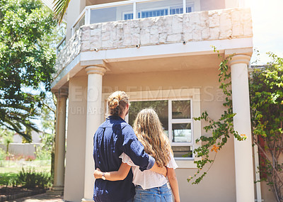 Buy stock photo Rearview shot of a young couple standing in front of their new home