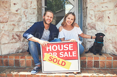 Buy stock photo Portrait of a young couple holding a for sale sign while sitting outside their new home