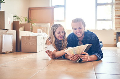 Buy stock photo Shot of a young couple looking at color swatches in their new home