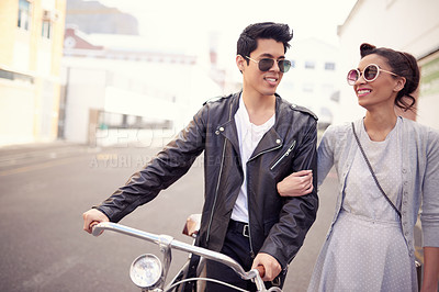 Buy stock photo Shot of a beautiful young couple taking a stroll together around the city