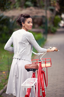 Buy stock photo Rearview shot of a beautiful young woman walking with a bicycle by her side through a park