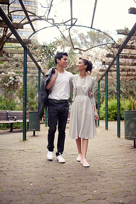 Buy stock photo Full length shot of a beautiful young couple a stroll together through the park