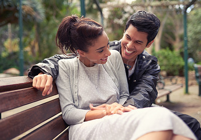 Buy stock photo Shot of a beautiful young couple sitting on a bench together at the park