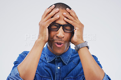 Buy stock photo Studio shot of a handsome young man looking stressed out against a grey background