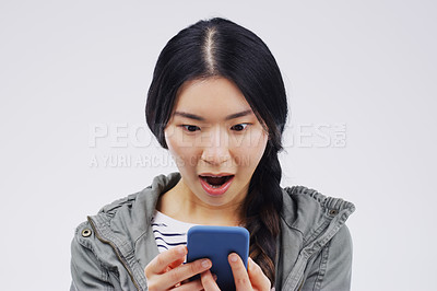 Buy stock photo Shot of a young woman looking surprised while reading something on her cellphone