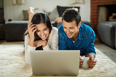 Buy stock photo Shot of an affectionate young couple lying down on the carpet and using a digital tablet together at home