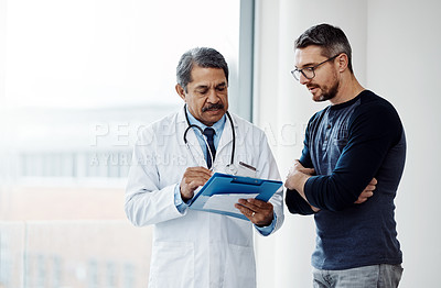 Buy stock photo Shot of a confident mature male doctor consulting a patient  inside a hospit