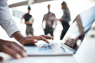 Buy stock photo Cropped shot of an unrecognizable businessman using a laptop while his colleagues stand in the background