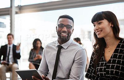 Buy stock photo Shot of two well-dressed businesspeople attending a conference