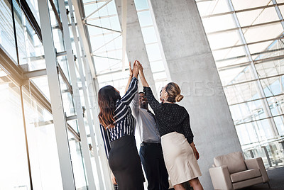 Buy stock photo Shot of a group of professional businesspeople high fiving in the office