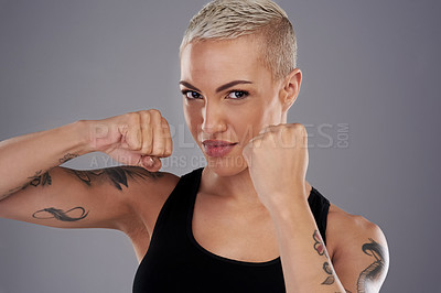 Buy stock photo Portrait of an athletic young woman holding up her fists to box while standing against a gray background