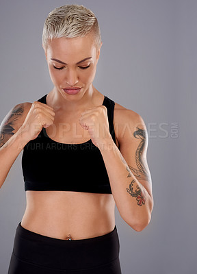 Buy stock photo Studio shot of an athletic young woman holding up her fists to box while standing against a gray background