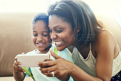 Buy stock photo Shot of a mother and her little son using a cellphone together at home