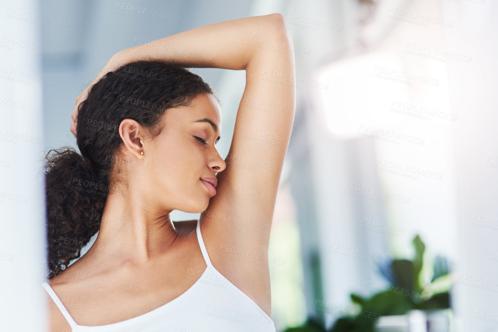 Buy stock photo Cropped shot of a young woman smelling her armpits in the bathroom at home