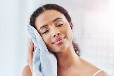 Buy stock photo Cropped shot of a young woman drying her face in the bathroom at home