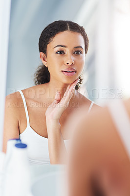 Buy stock photo Cropped shot of an attractive young woman touching her face during her morning routine