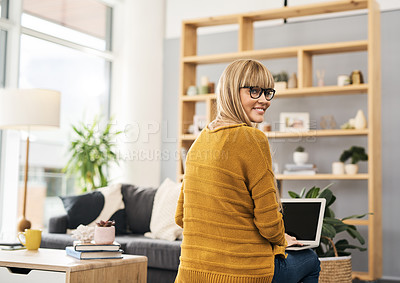 Buy stock photo Shot of a young woman using her laptop while relaxing in the living room at home