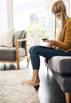 Buy stock photo Shot of a young woman using a laptop and credit card on the sofa at home