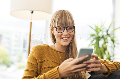 Buy stock photo Shot of a young woman using a mobile phone on the sofa at home