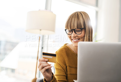 Buy stock photo Shot of a young woman using a laptop and credit card at home