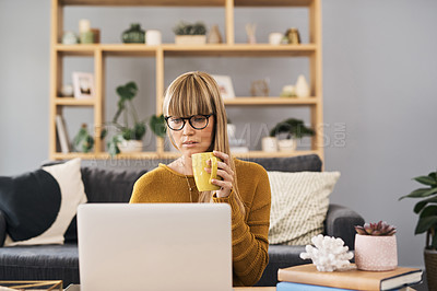 Buy stock photo Shot of a young woman using her laptop and having coffee in the living room at home