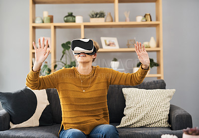 Buy stock photo Shot of a young woman using a virtual reality headset on the sofa at home