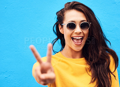 Buy stock photo Shot of a attractive young woman showing the peace sign while  posing against a blue background