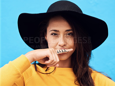 Buy stock photo Shot of a attractive young woman holding her finger on her upper lip to pretend she has a moustache against a blue background