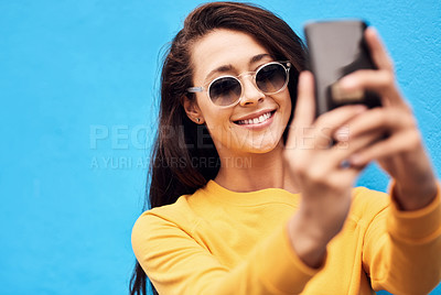 Buy stock photo Shot of a attractive young woman taking a selfie while standing against a blue background
