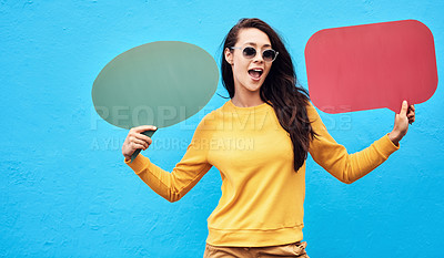 Buy stock photo Shot of a attractive young woman holding two speech bubbles while standing against a blue background
