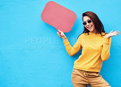 Buy stock photo Shot of a attractive young woman holding a speech bubble while standing against a blue background