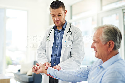 Buy stock photo Cropped shot of a focused middle aged doctor taking a blood pressure test on a patient inside of his office during the day