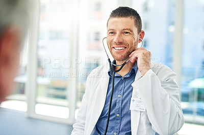 Buy stock photo Cropped shot of a confident middle aged doctor wearing a stethoscope while listening to a patient's heartbeat