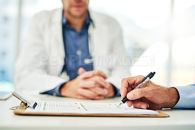 Buy stock photo Cropped shot of an unrecognizable man signing a form that a doctor presented inside of his office during the day