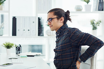 Buy stock photo Shot of a young designer suffering with back pain while working in an office