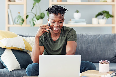 Buy stock photo Shot of a young man talking on a cellphone while using a laptop at home
