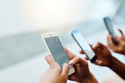 Buy stock photo Closeup of a group of businesspeople texting on their cellphones inside of the office during the day