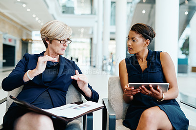 Buy stock photo Shot of two businesspeople having a discussion together while being seated inside of a office building during the day
