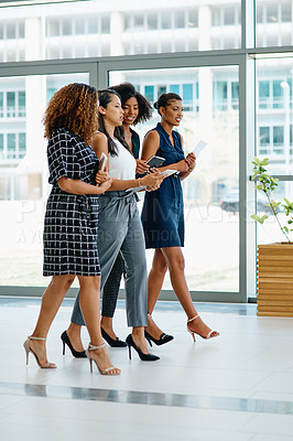 Buy stock photo Shot of a group of young businesswomen walking together inside of a office building during the day